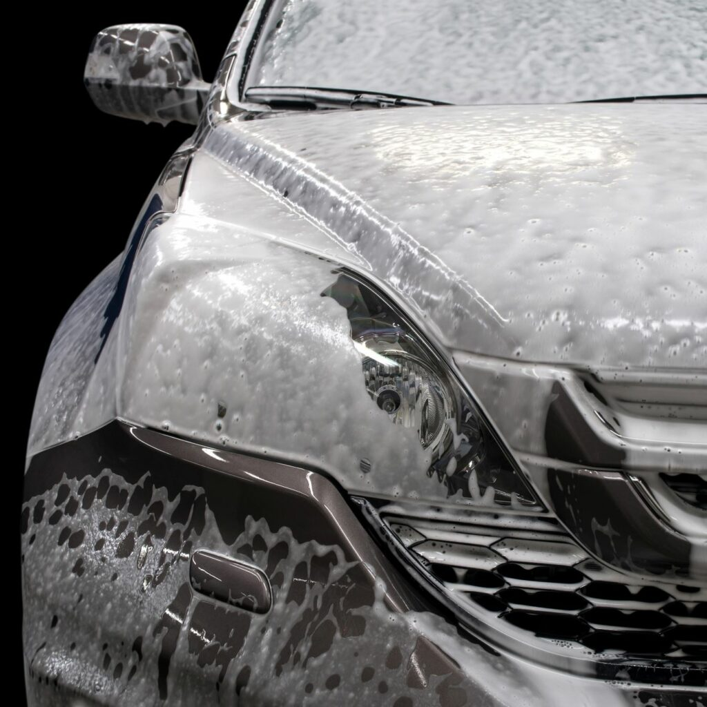 An up-close shot of a soapy car.