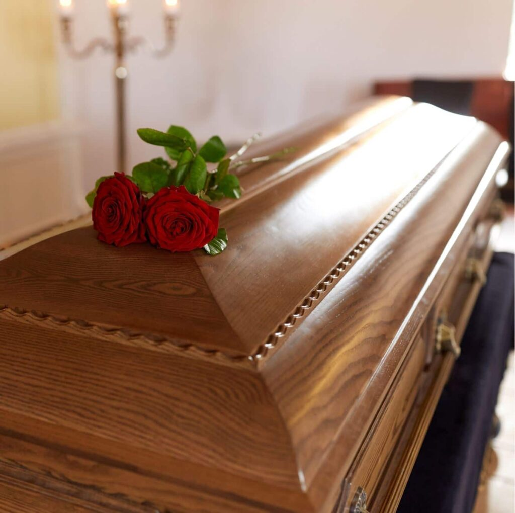 A coffin with roses lying on top.