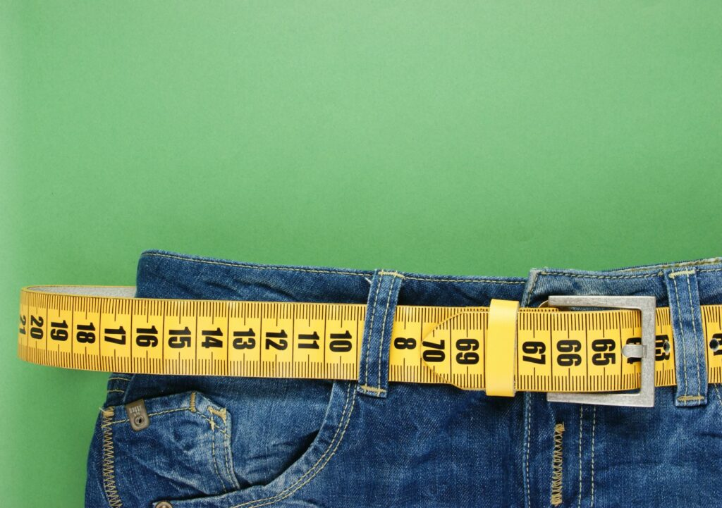 A pair of jeans with a tape measure running through the belt loops.