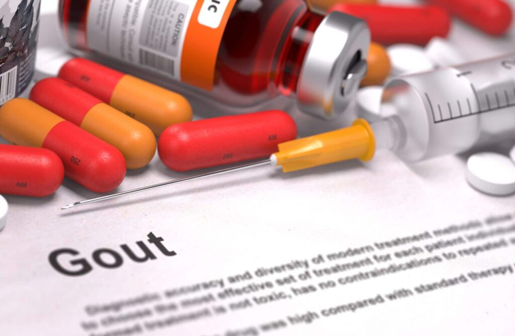 The definition of gout on paper surrounded by medicine.