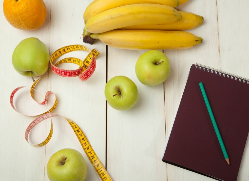 Fruits, a tape measure, and a journal on a wood table.