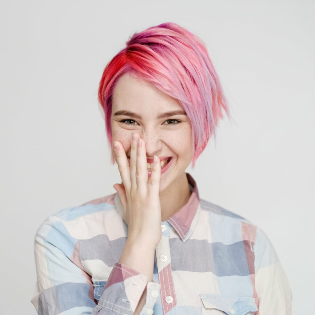 A woman smiling and laughing with a pink pixie cut hairdo.