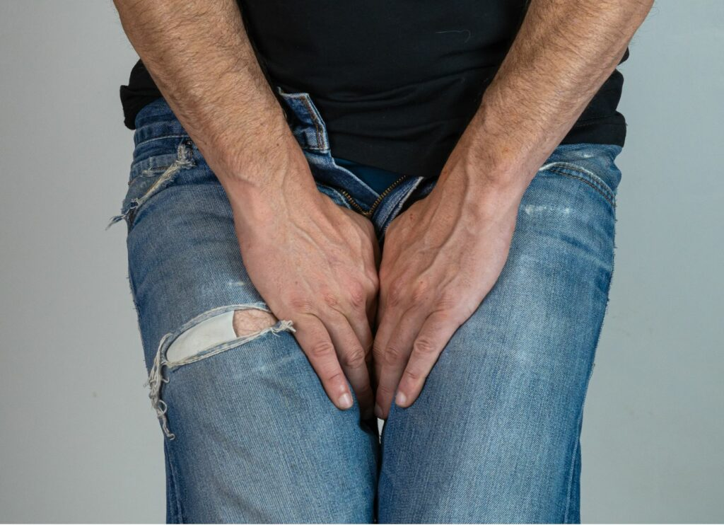 A man holding his legs near his genital area.