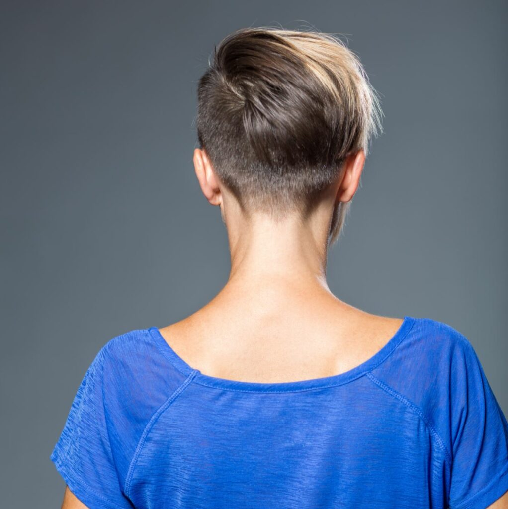 The back of a woman's head with a short undercut hairstyle.