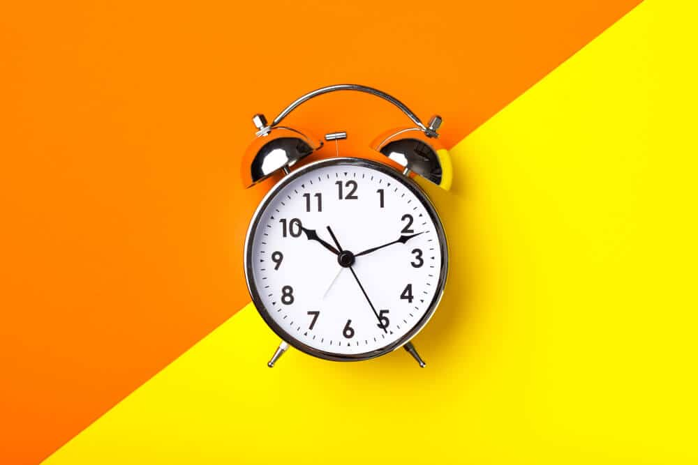 retro alarm clock on half orange and yellow background
