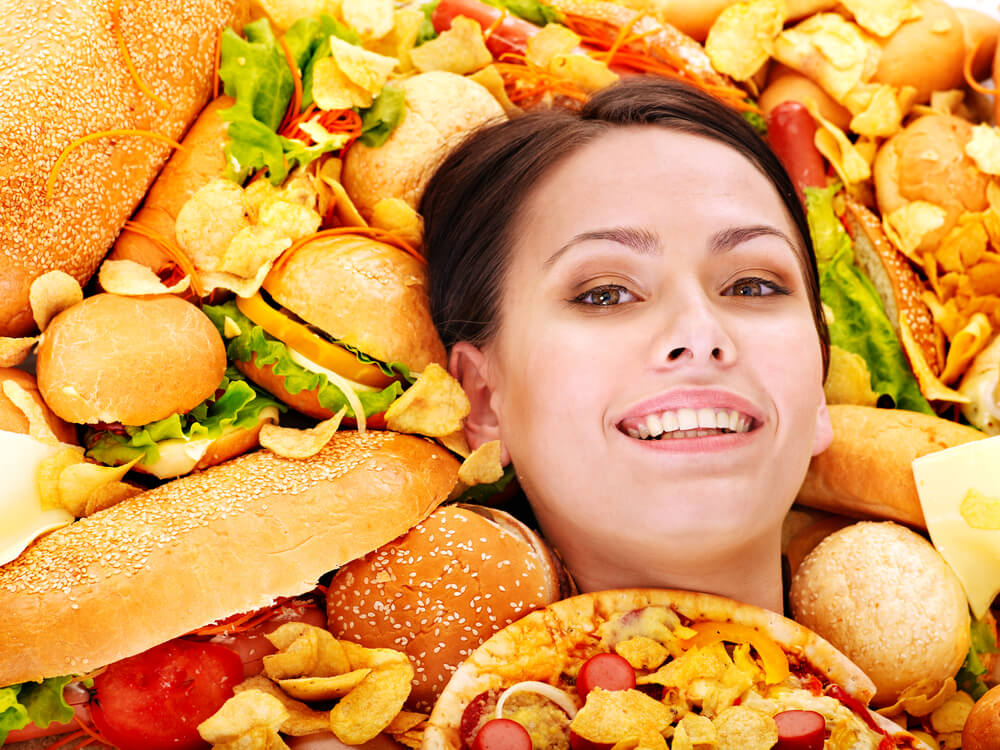 Woman's head pokes out of unhealthy food pile
