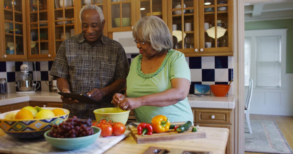 Retired black couple cooking in the kitchen