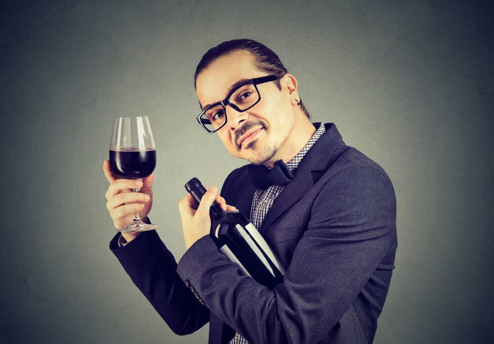 Funny man in suit and glasses embracing bottle of wine holding wineglasses
