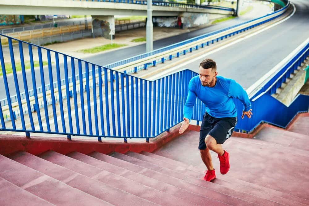 Athletic man doing interval training running on stairs in urban setting