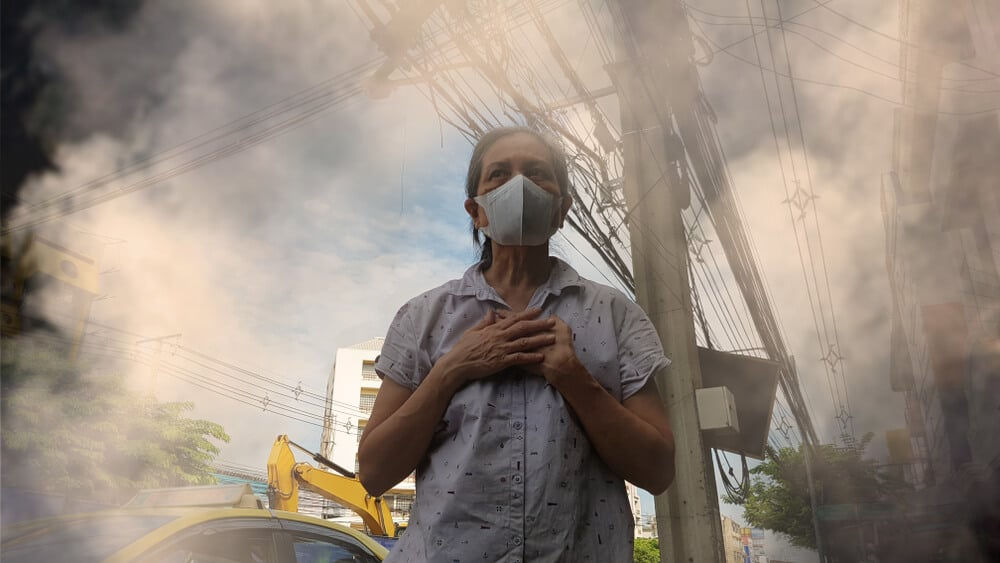 Old woman wearing mask for protect air pollution (PM2.5) in the city. PM2.5 caused health problem and respiratory system disorder as lung cancer, allergy, asthma, restictive lung disease.