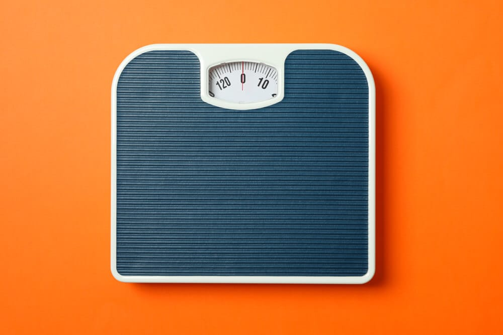 weigh scales on orange background, top view