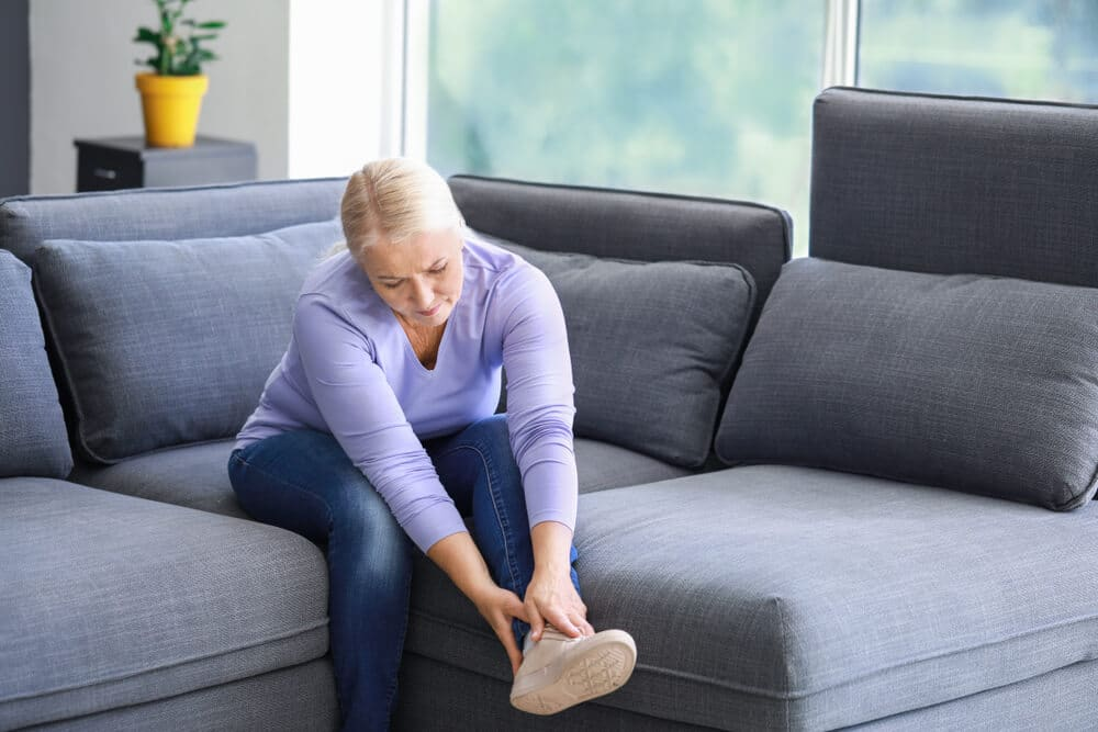 Mature woman suffering from pain in leg at home