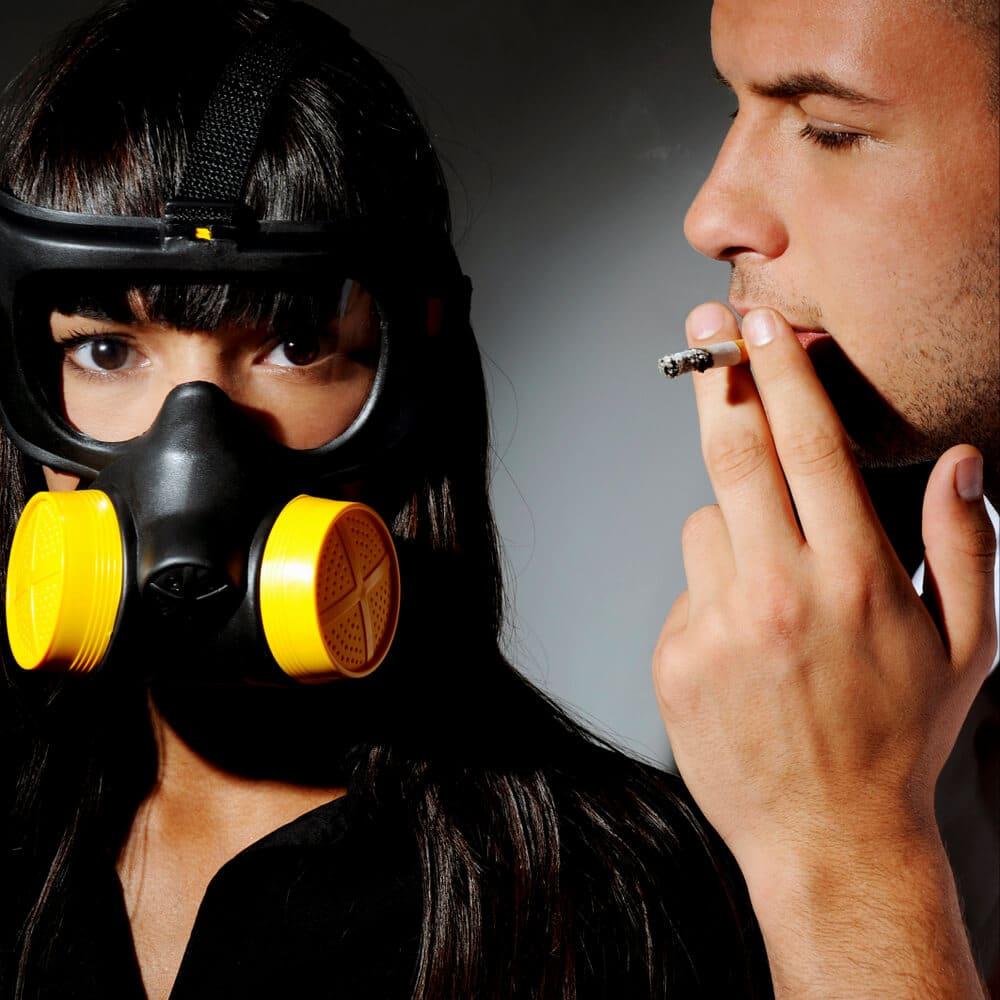Non smoker standing next to a smoker, studio shot