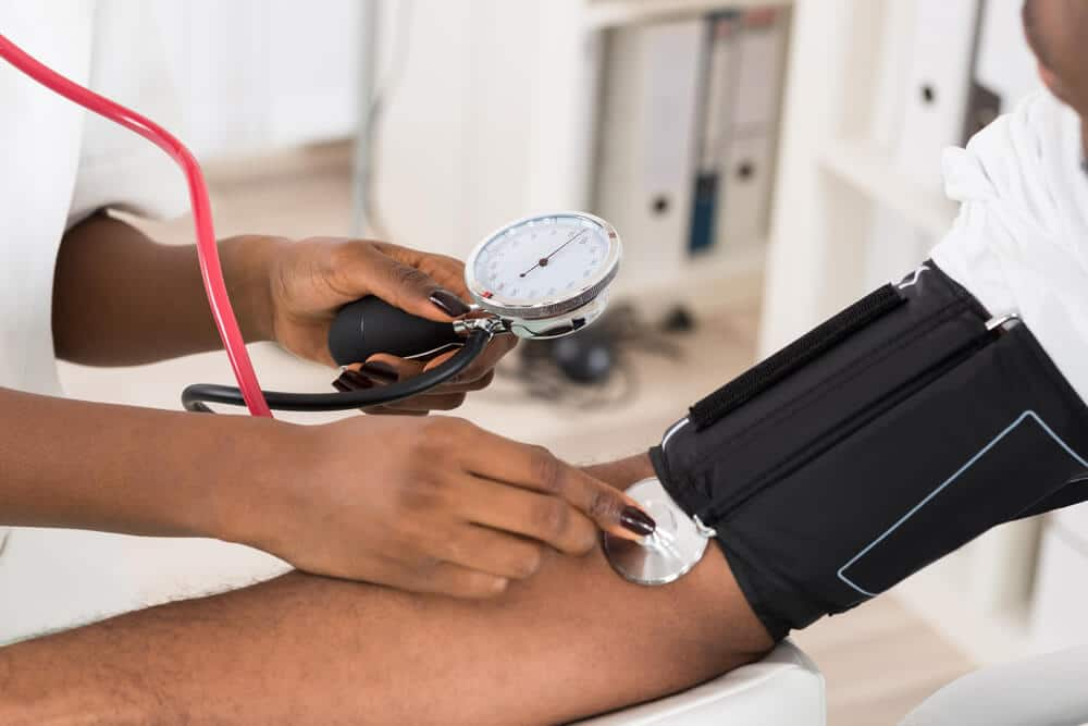 Close-up Of Doctor Measuring Patients Blood Pressure With Stethoscope