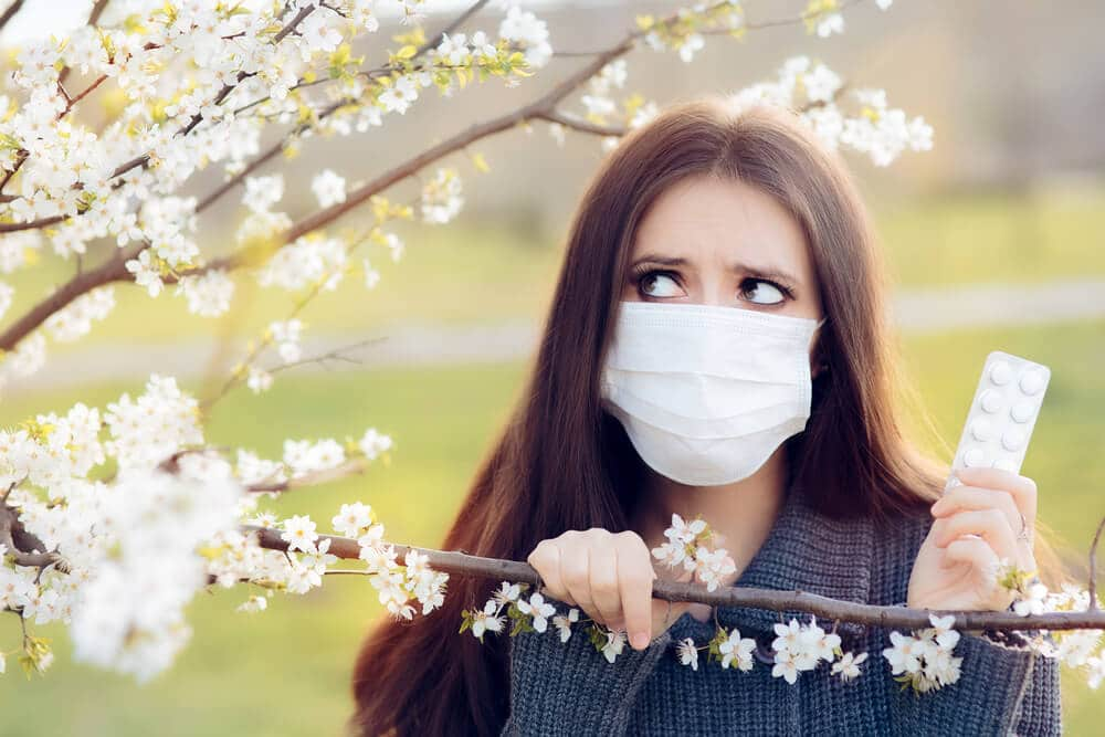 Woman with Respirator Mask Fighting Spring Allergies Outdoor - Portrait of an allergic woman surrounded by seasonal flowers wearing a protective mask