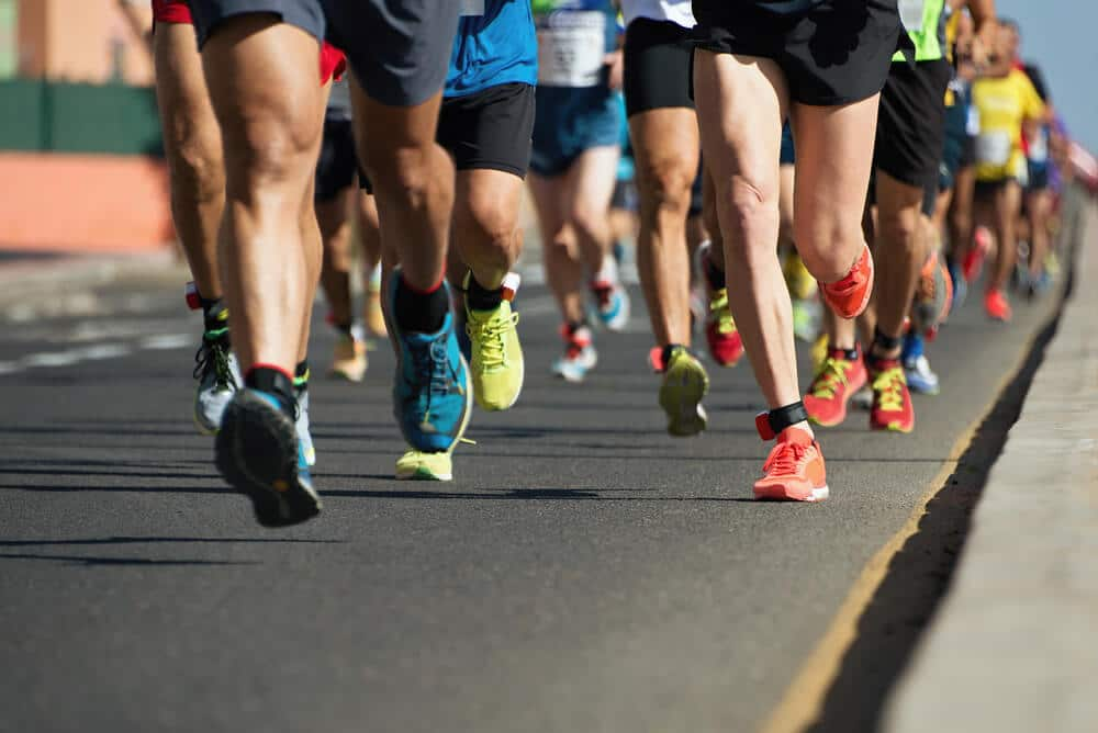 Marathon running in the light of evening,running on city road detail on legs