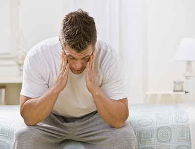 Tired man sits on bed with head in hands