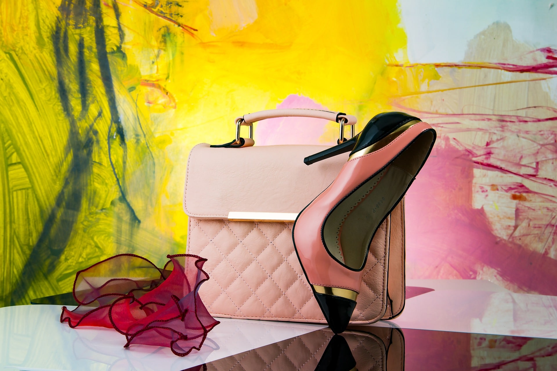 A pink designer handbag sits on a glossy table next to a stiletto and ruffled fabric