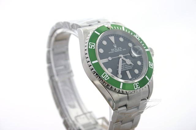 A silver and green Rolex wristwatch showing the face