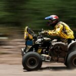 A man in yellow gear rides an ATV along a dirt track