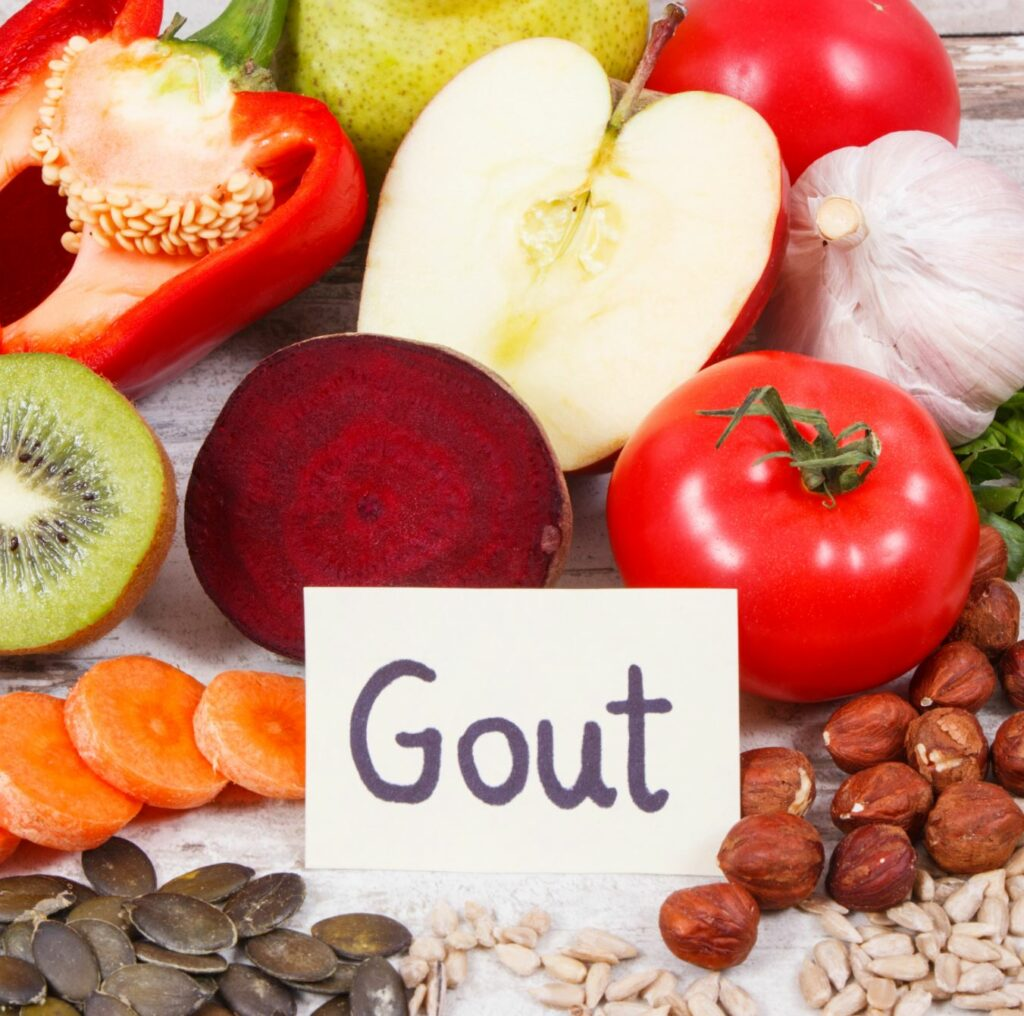 A sign with Gout on it surrounded by fruits and vegetables.