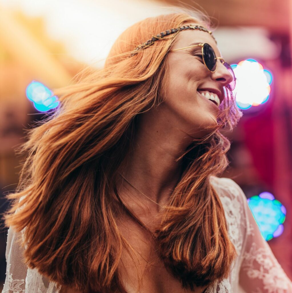 An up close shot of a woman smiling and dancing.