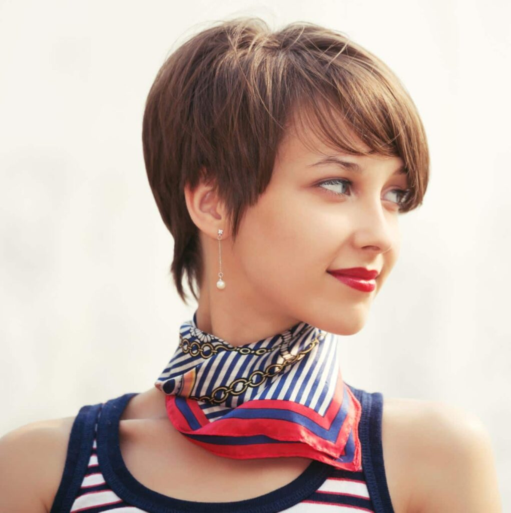 A woman with a short layered pixie cut looking off to the side.