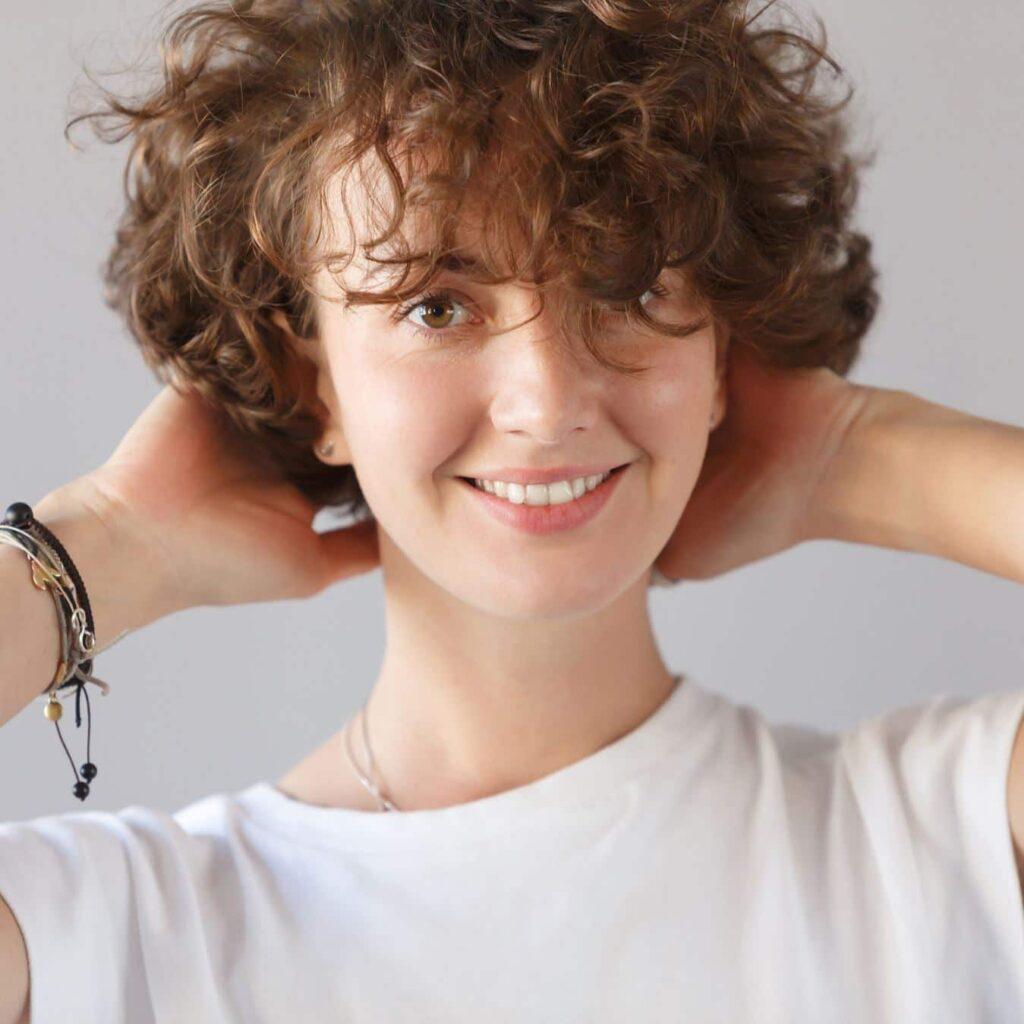 A woman smiling with short curly hair with bangs.