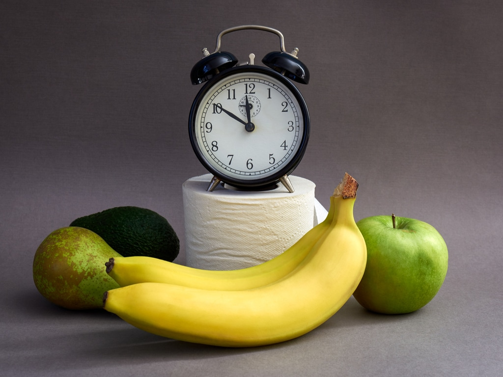 An alarm clock, toilet paper, and fruits.