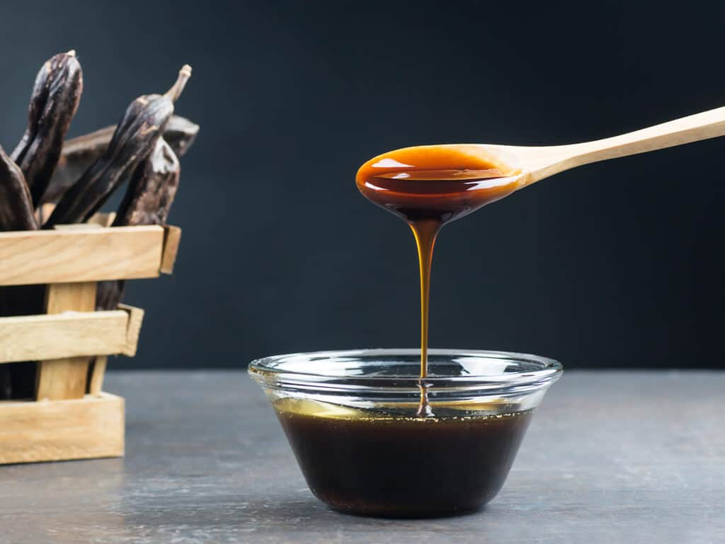 A wooden spoon with a bowl of molasses underneath.