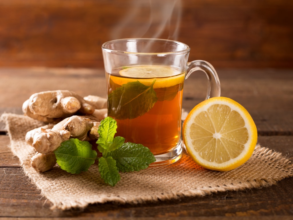 A cloth with ginger, lemon, mint, and tea on top of it.