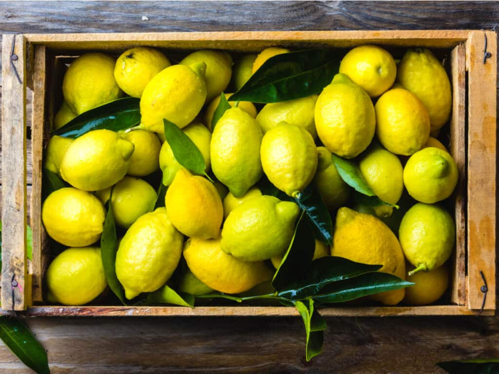 A wooden box filled with lemons.