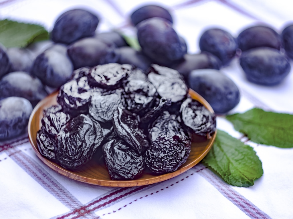 A plate of dried prunes on top of a plaid surface.
