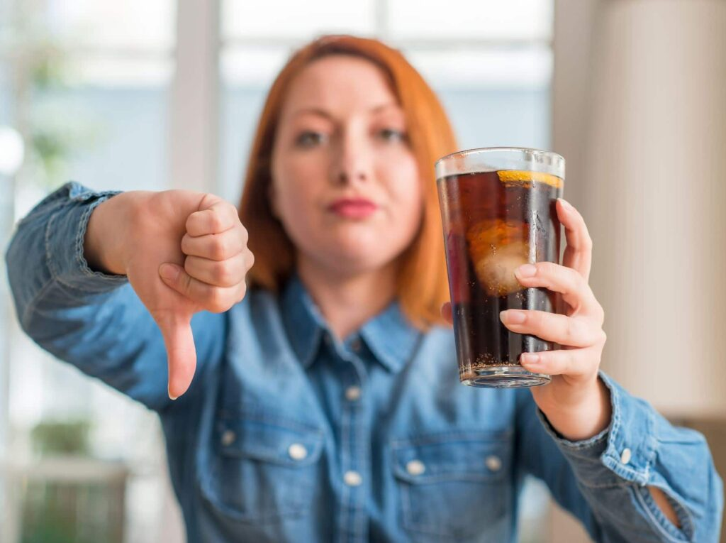 A woman holding a glass of soda with a thumbs down.