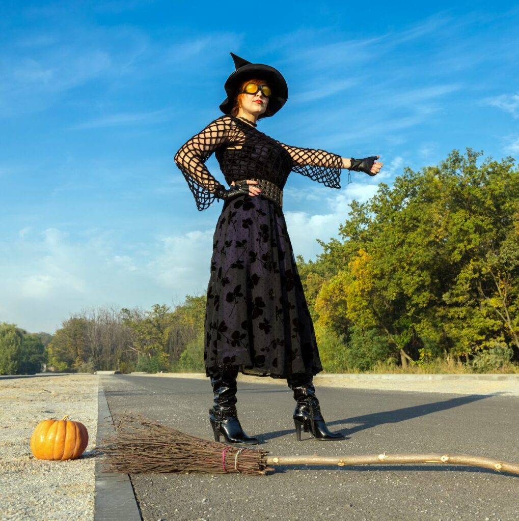 A witch standing on the side of the road hitch hiking.