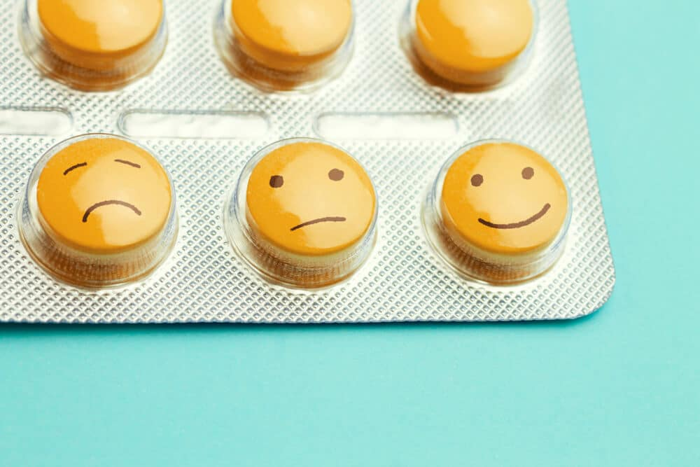 Orange pills and funny faces in a blister on a blue background. The concept of antidepressants and healing