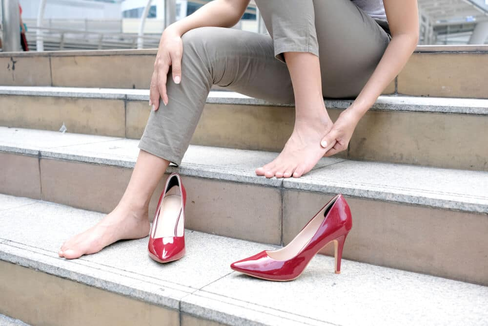 Woman sitting on staircase Catch her foot and she has foot pain. Caused by wearing high .Health and beauty concepts