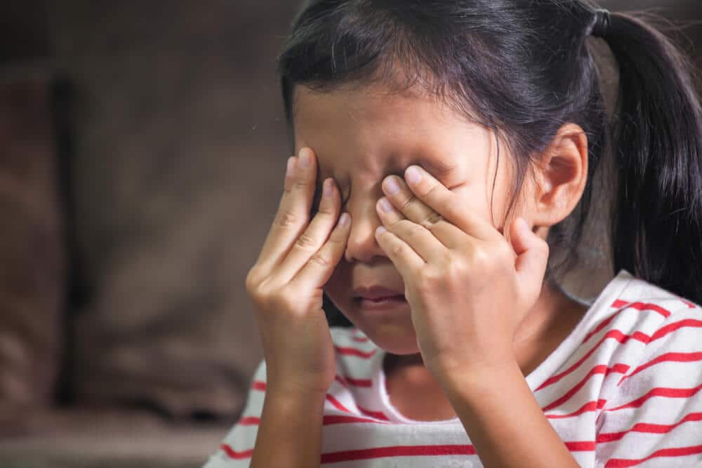 Sad asian child girl is crying and rubbing her eyes with her hands