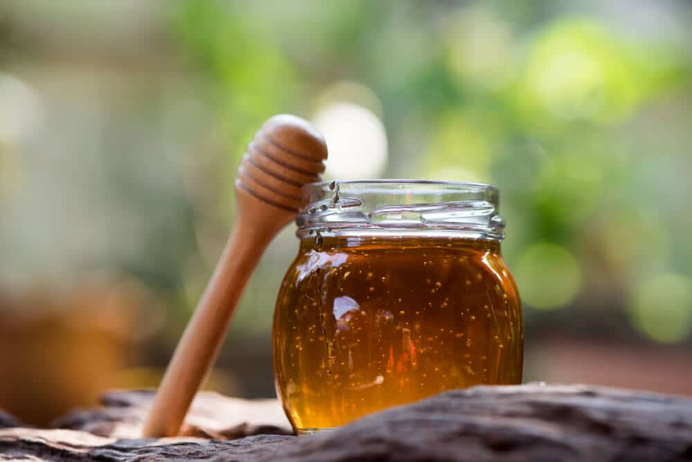 Honey in a glass bottle on a natural background and has medicinal properties