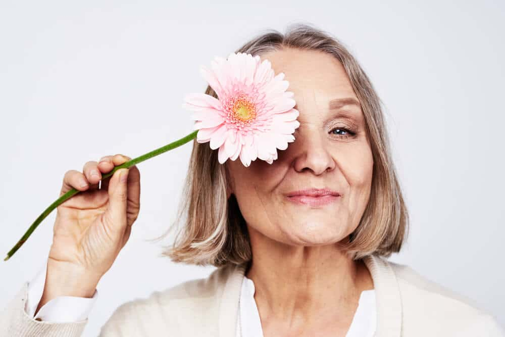 Cheerful elegant elderly woman holding a flower near the face on a gray background S