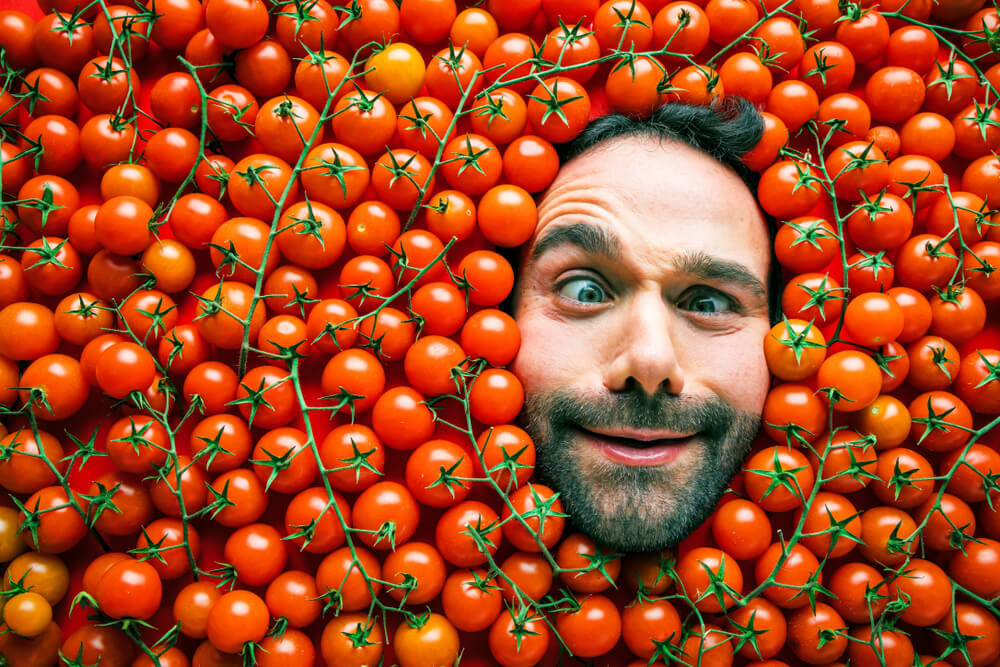 Man with tomatoes, concept for food industry. Face of laughing man in tomato surface.