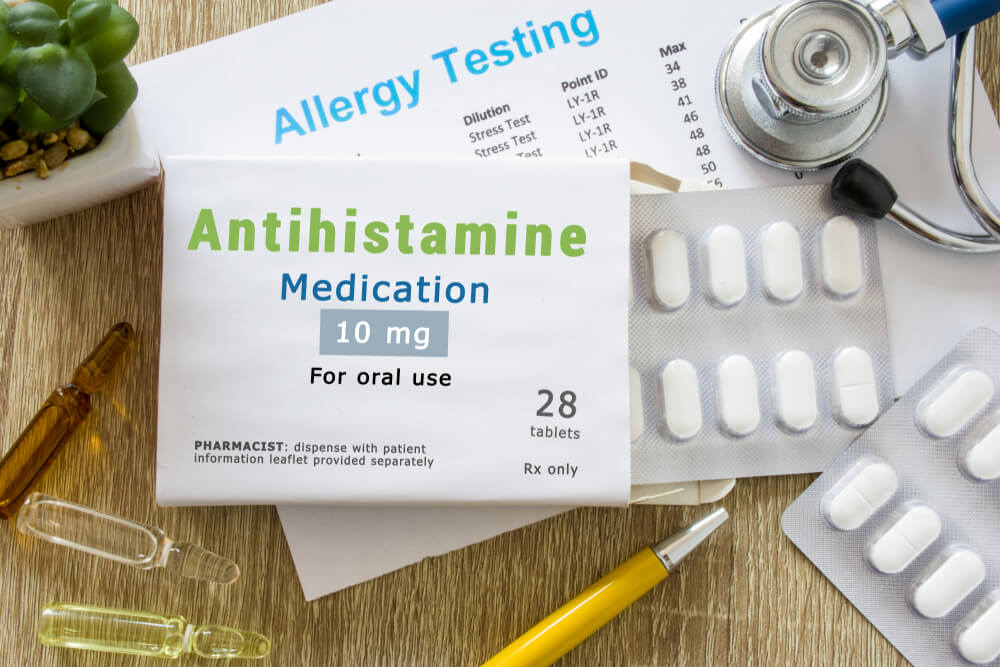 """KYIV, UKRAINE-MAY 13, 2019: Antihistamine medication or allergy drug concept photo. On doctor table is pack with word """"Antihistamine medication"""" and pills for treatment of allergy and hypersensitivity"""