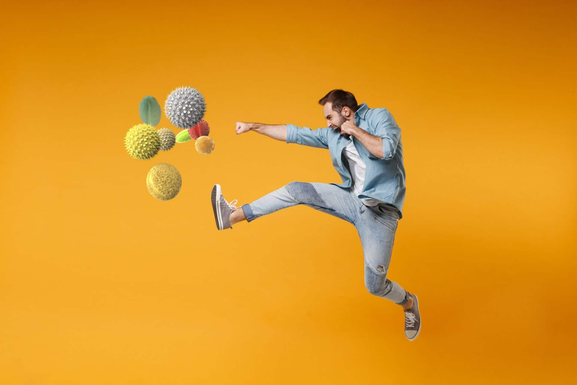 A white man jump kicks common allergens against a bright orange background. Hay fever treatment and allergic rhinitis management concept