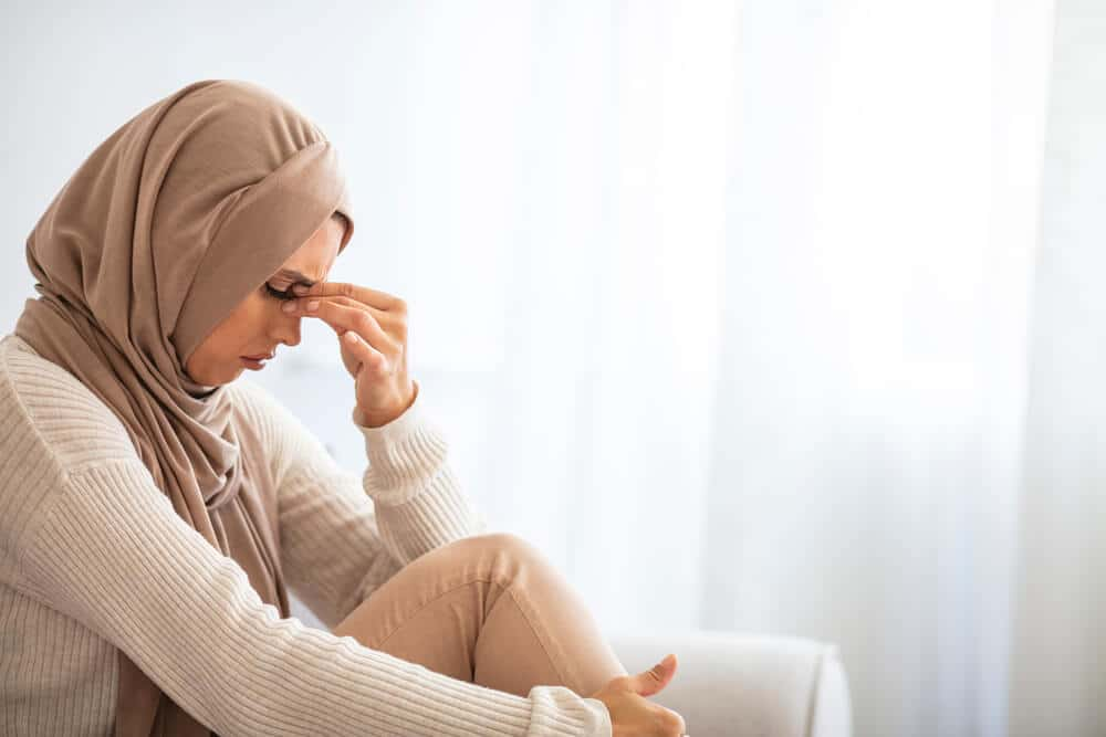 Sad Muslim woman holds her head while depressed