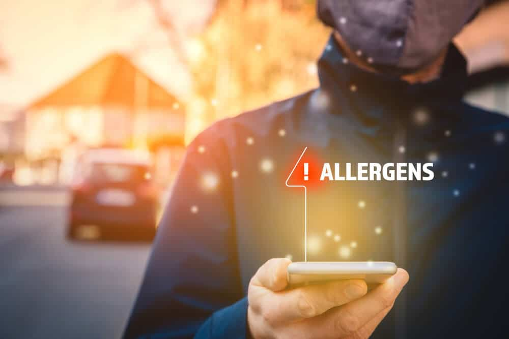 Increased concentration of allergens and polls in the air. Man with mask and smart phone with notification or report about allergens. Modern healthcare concept.