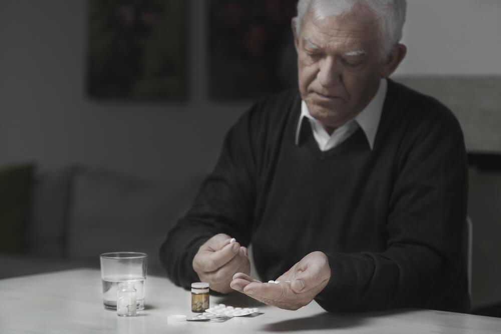 Senior sad man taking a lot of medicines