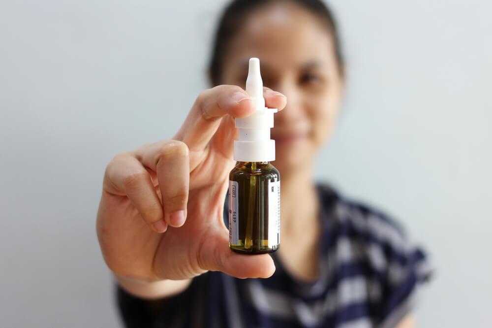 Nasal Spray, Female hand spraying nasal spray with blurred background