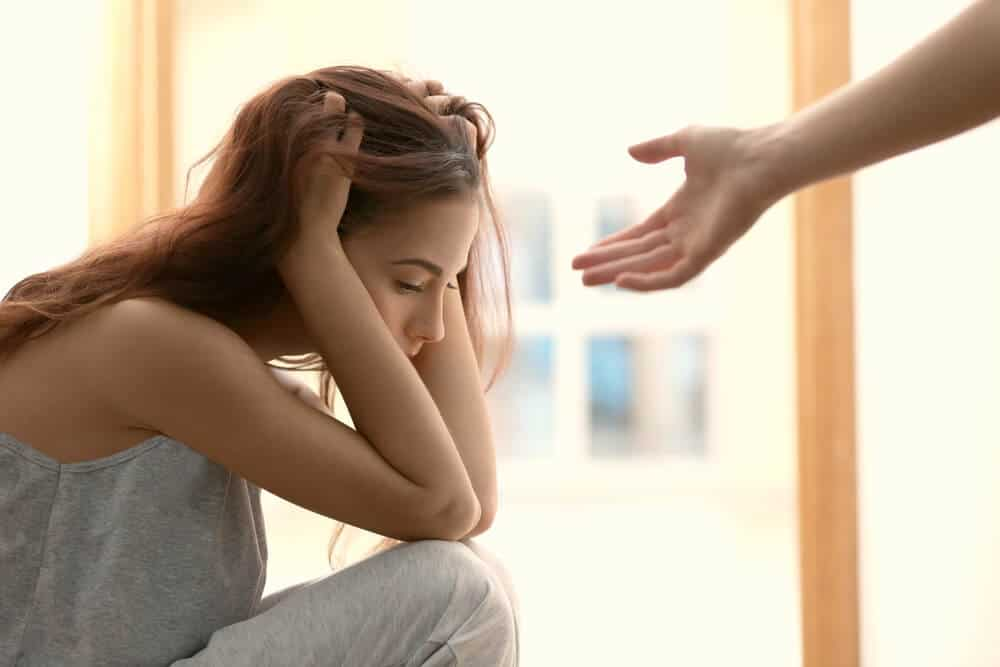 Someone giving hand to depressed woman at home