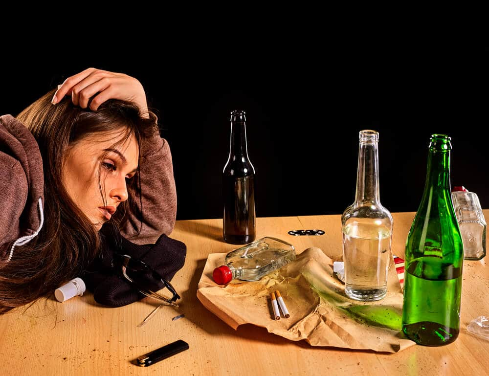 Woman alcoholism is social problem. Female drinking is cause of nervous stress . She in hood and hat with green alcohol bottle in bad mood . Drunken woman falls asleep on dirty table black background.