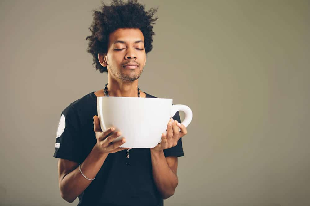 man holding a funny huge and oversized cup of black coffee in caffeine addiction concept